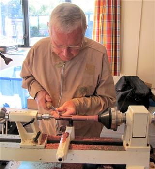 Keith Leonard turning part of a drop spindle
